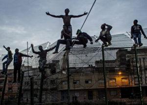 SERGI CÁMARA | Subsaharians intentant escalar la doble barrera prop de Beni Enza a Melilla el mars del 2014, dins de l'exposició <em>Els murs del poder</em>