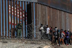 © Guillermo Arias / AFP | Migrants centreamericans miren a través del tancat vigilat per guardes fronterers estatunidencs prop d'El Chaparral, a Tijuana, el 25 novembre del 2018