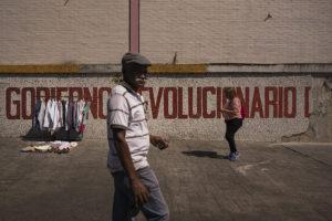 © ADRIANA LOUREIRO FERNÁNDEZ | Un home passa per davant d'una parada de roba d'ocasió en un carrer de Caracas, el febrer del 2019