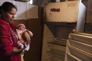 © ANDREA LOUREIRO FERNÁNDEZ | Zuleima Pérez amb el seu nadó davant d'una nevera avariada a El Valle, Caracas, el 2017