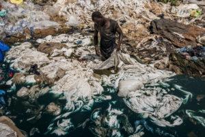 © Frédéric Noy |Un home prop de Katabi, Uganda, neteja amb colorant blau plàstics en un pantà del llac Victòria, el que acabarà contaminant tota l'aigua