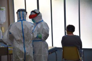 ÈLIA PONS | Dos sanitarios del centro de primaria Raval Nord de Barcelona, equipados con EPI por el coronavirus, atienden a un paciente