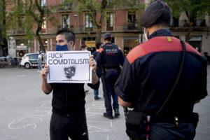 ALBERT SALAMÉ/VILAWEB | Manifestant dans la place de la Vila de Gràcia de Barcelona avec un affiche de rejet fusionnant les paroles Covid et capitalisme, et un membre de la police catalane prenant note de son identité