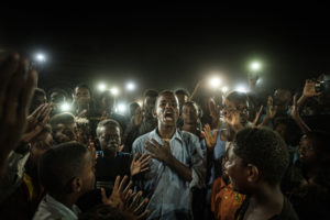 YASUYOSHI CHIBA/AFP | Un jeune homme récite une poésie de combat à Khartum, le 19 juin 2019, semaines après la chute du dictateur soudanais Omar al-Bashir (photo primée avec le World Press Photo 2020)
