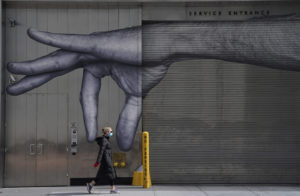 TIMOTHY A. CLARY/AFP | Une femme masquée passe devant ce graffiti peint dans un mur à New York, en une image du 22 avril 2020 présent à l'exposition Pandèmie(s)