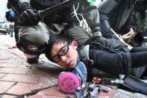 ANTHONY WALLACE/AFP | Manifestant arrêté à terre à Hong Kong le premier octobre 2019, journée du 70 anniversaire de la création de la République Populaire de la Chine