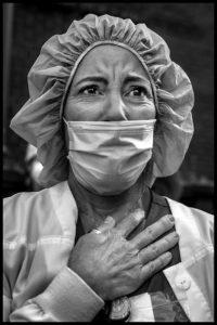 PETER TURNLEY | Erika, infirmière volontaire brésilienne nationalisée états-unienne, écoute émue l'hymne <em>America the beautiful</em> devant l'hôpital Lenox Hill