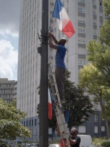ARCHIVE | Une image symbolique de <em>Nous</em>, avec des drapeaux français qui président une cité de la périphérie parisien