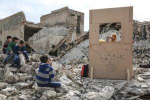 ANAS ALKHARBOUTLI/DPA/UNOCHA | Des enfants syriens regardent un spectacle de marionnettes au milieu des runes dans la ville de Saraqib, dans la province du nord-ouest d'Idleb, en mars 2019