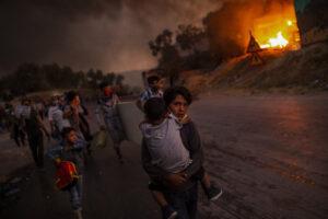 ANGELOS TZORTZINIS/AFP | Des réfugiés dans le camp de Moria, sur l'île grecque de Lesbos, fuyant les flammes, le 9 septembre 2020