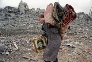 ÉRIC BOUVET | Una dona travessa la destruïda plaça Minutka, a l'entrada sud de Grozni, al febrer del 2000, portant el retrat del seu marit mort en una nova ofensiva de Rússia a Txetxènia en què també ha perdut els seus dos fills. Bouvet no va aconseguir publicar aquesta foto en el seu moment