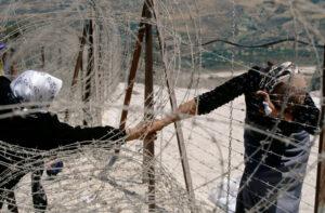 ÉRIC BOUVET | Dues dones palestines se saluden a través del filat a Dhaira, a la frontera entre el Líban i Israel, al maig del 2000, després de 22 anys d'ocupació dels israelians del sud del Líban